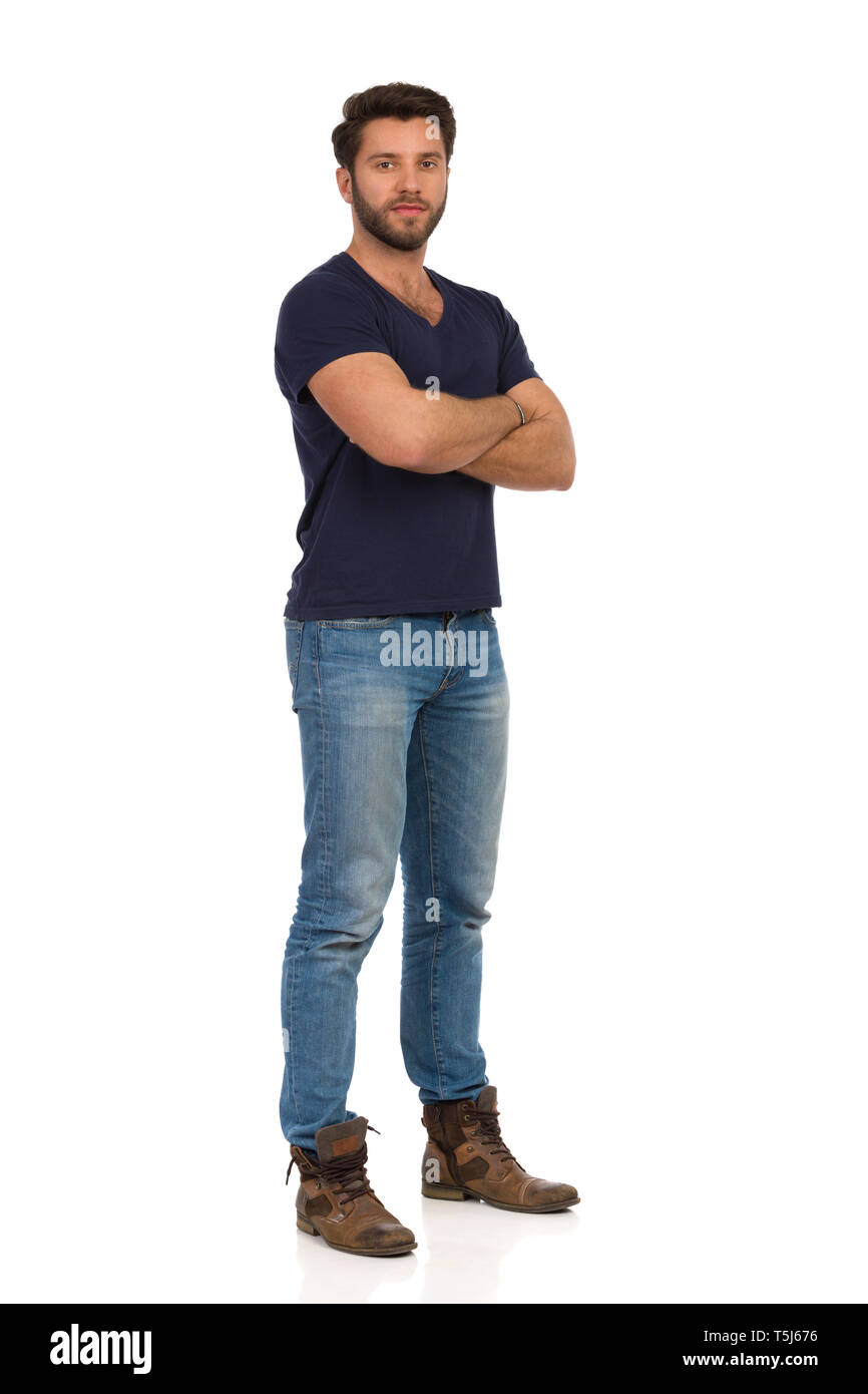 Serious handsome man in boots, jeans and blue t,shirt is
