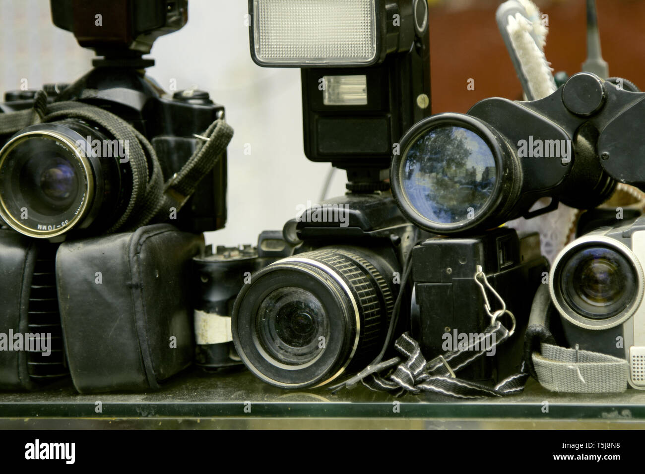 old photo equipment is dusty and not in demand. SLR cameras and flashes - Stock Image