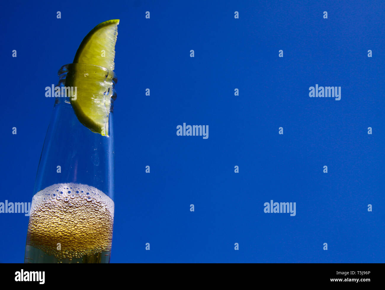 Close up of isolated bottleneck with sparkling yellow beer and a slice of lime against cloudless deep blue sky - Stock Image
