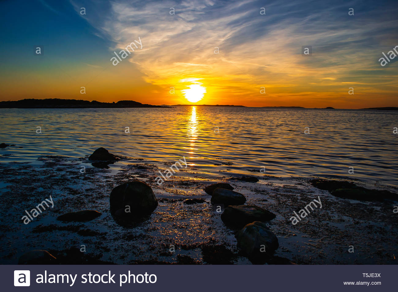 Colorful sunset by the calm sea. Beautiful shining light and reflections on the water in the dark evening. Coastal environment, magical atmosphere. - Stock Image