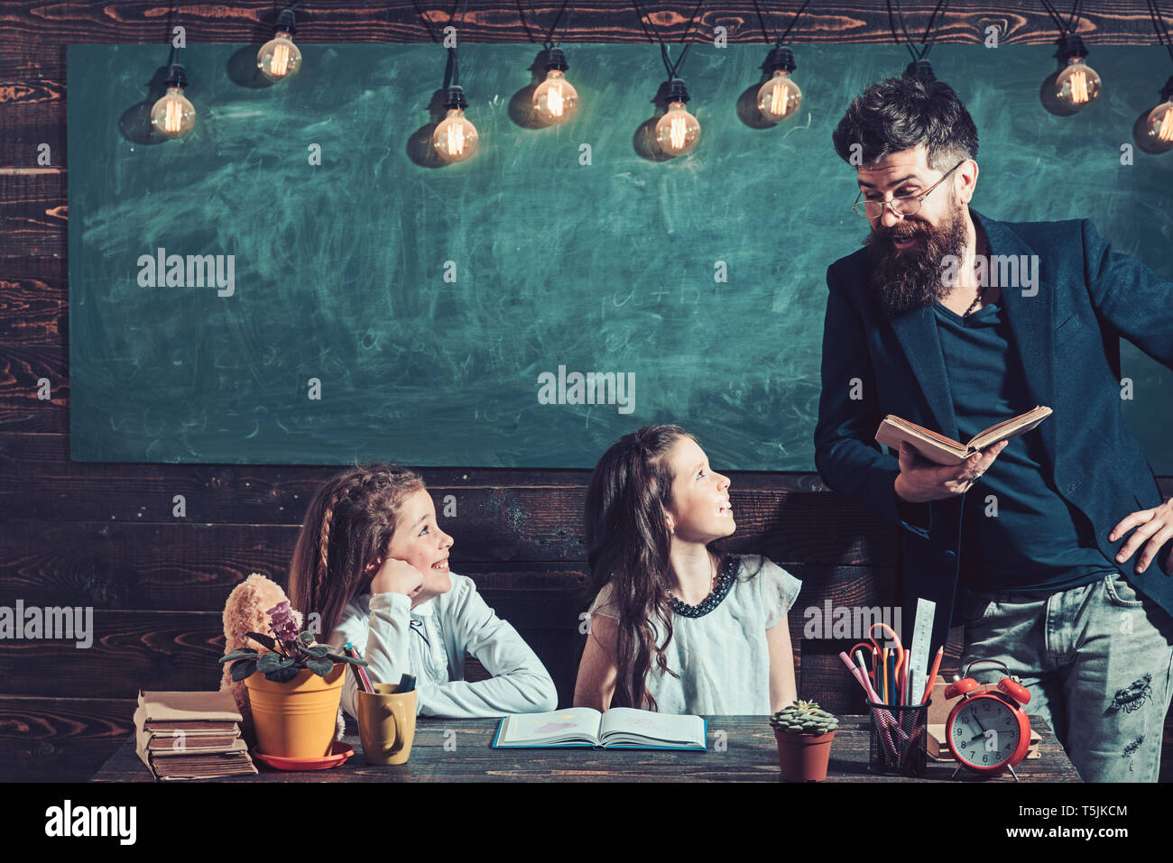 Teacher working with young schoolgirls at desk in class - Stock Image