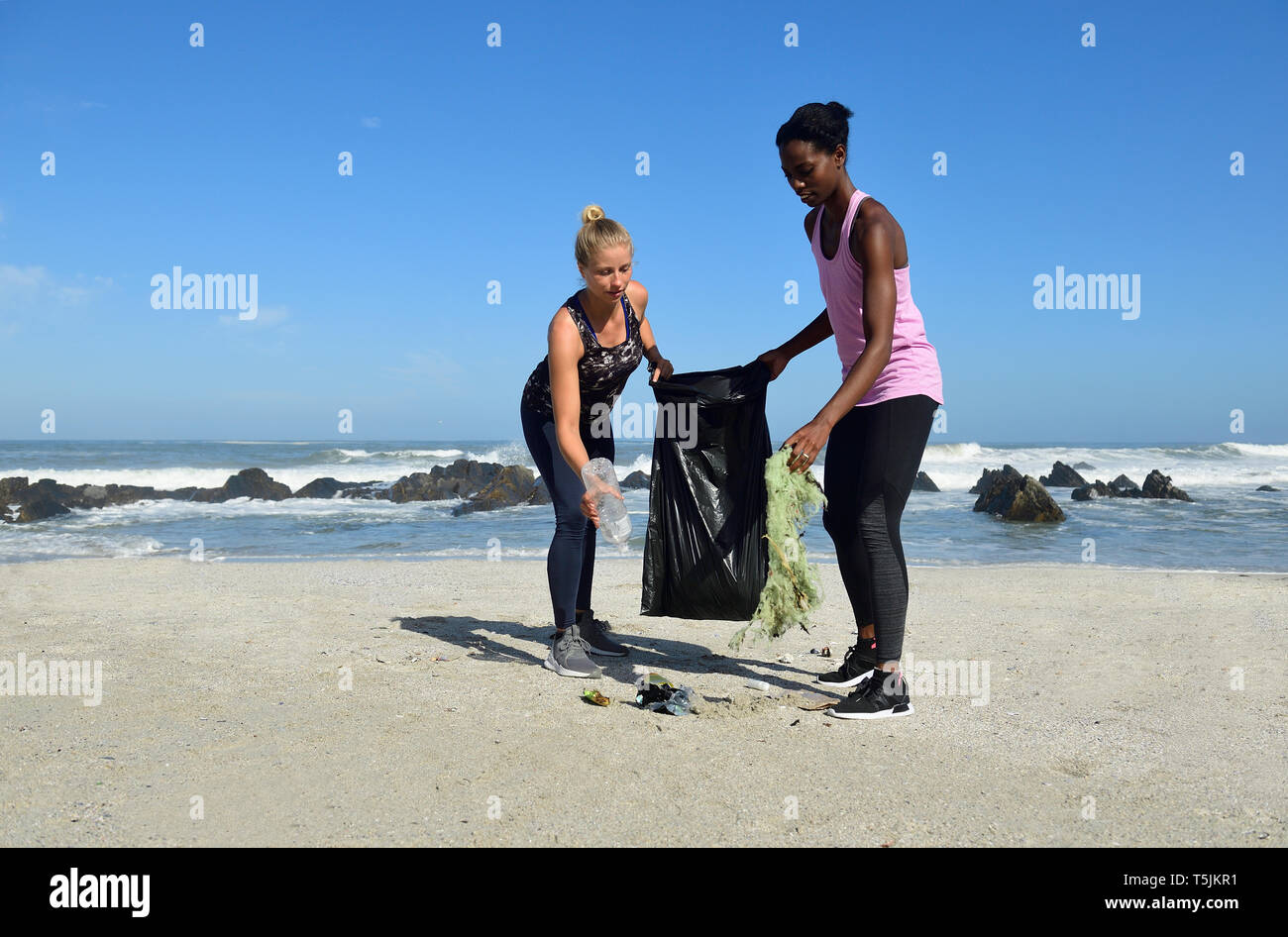 Two women cleaning the beach from plastic waste - Stock Image