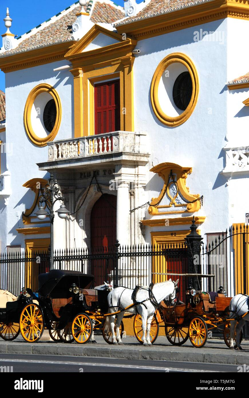 View of the bullring with horse drawn carriages in the foreground, Seville, Seville Province, Andalusia, Spain, Europe. - Stock Image