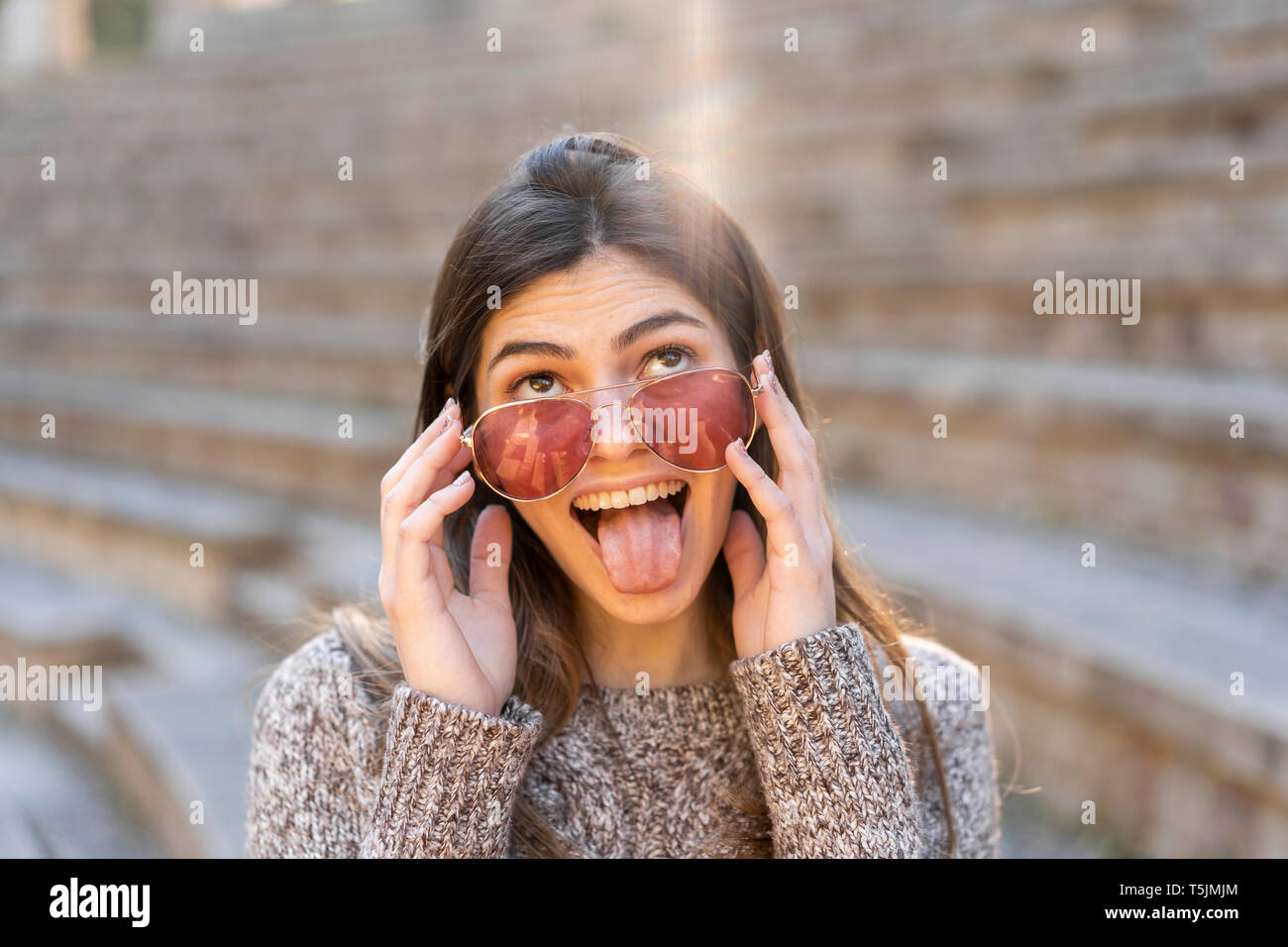 Playful young woman wearing sunglasses and grimacing - Stock Image