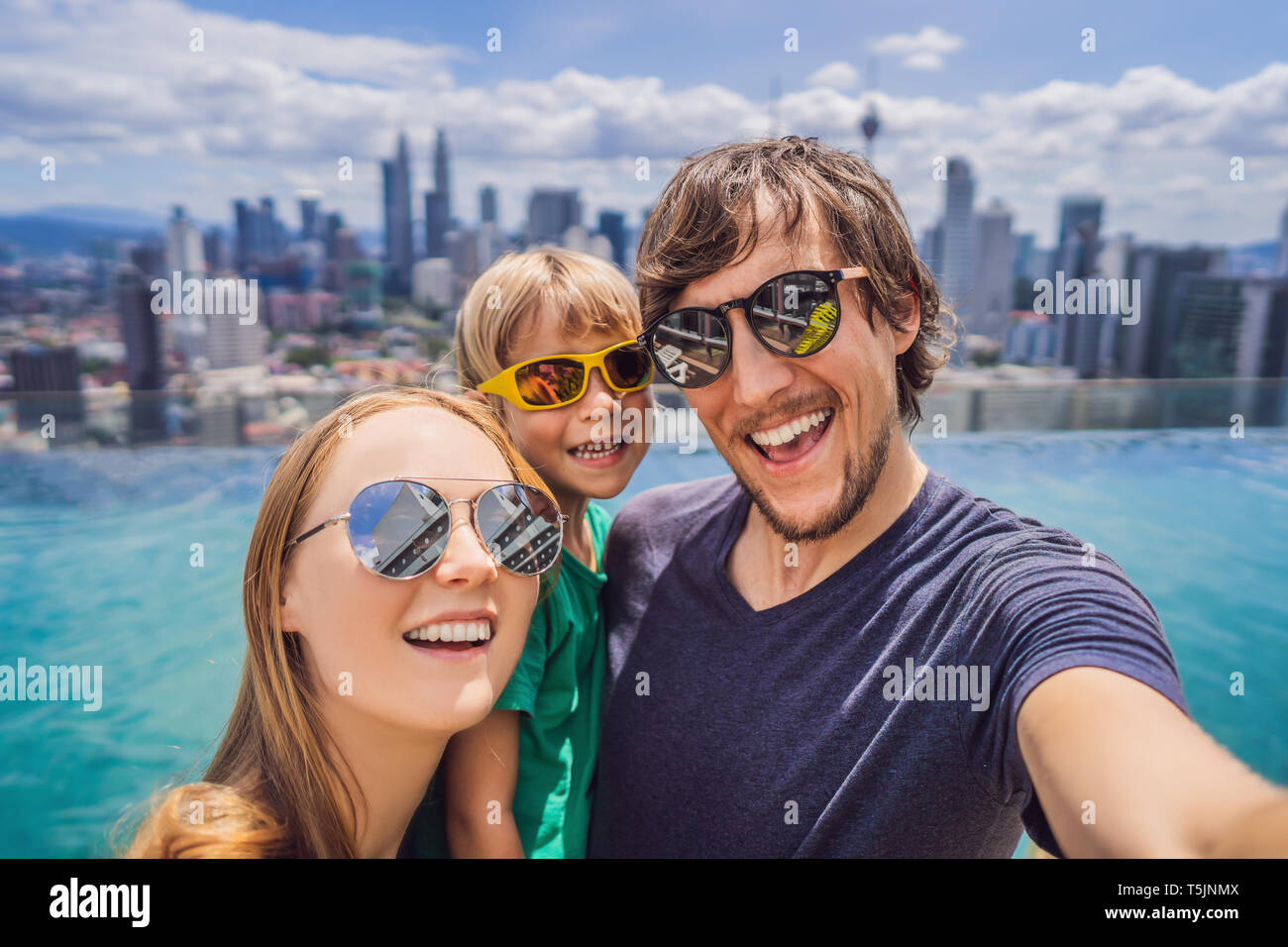 Vacation and technology. Happy family with kid taking selfie together near swimming pool with panoramic views of the city - Stock Image