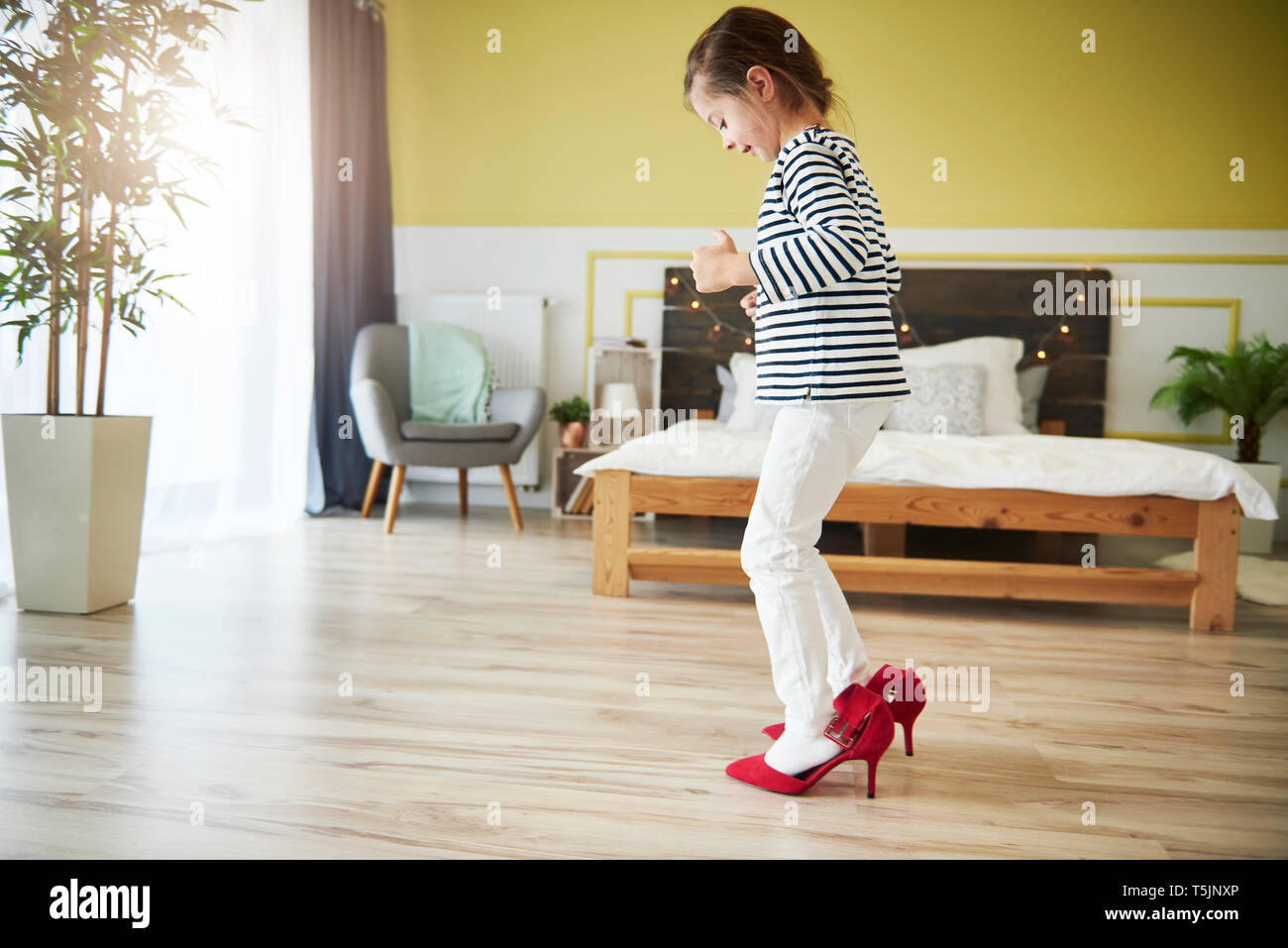 Little girl dressing up, wearing mother's red high heels - Stock Image