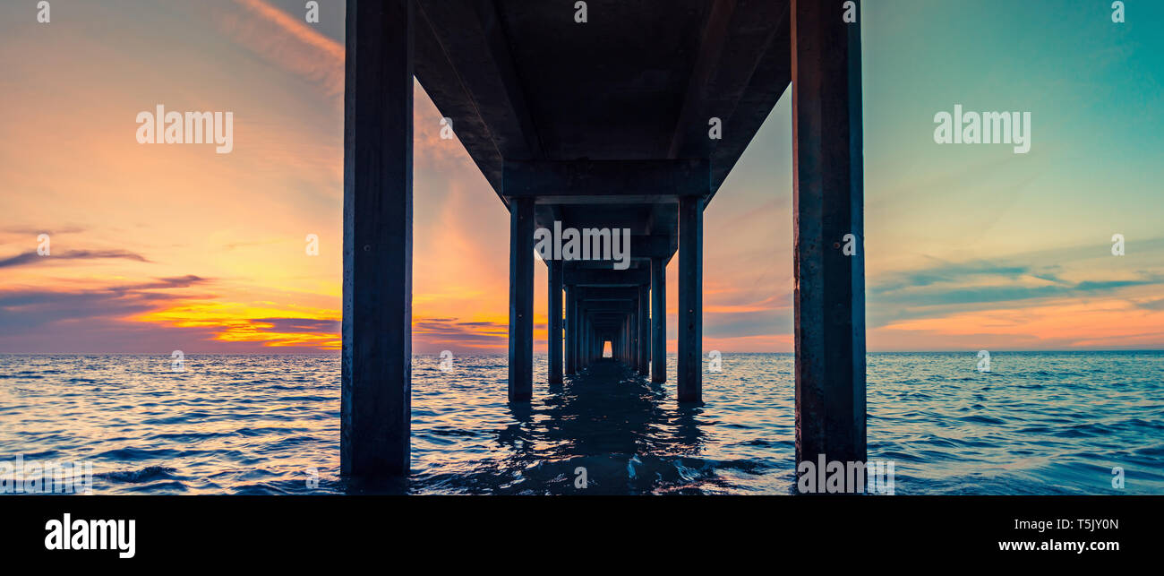 Under Brighton pier perspective view at sunset, South Australia - Stock Image