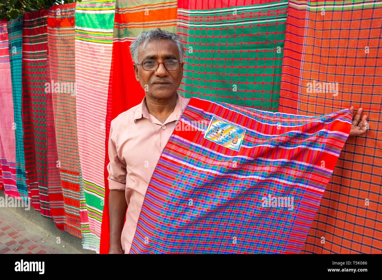 A Bangladeshi vendor sits under his display of traditional towels or gamcha as he waits for customers on a street of Dhaka. - Stock Image