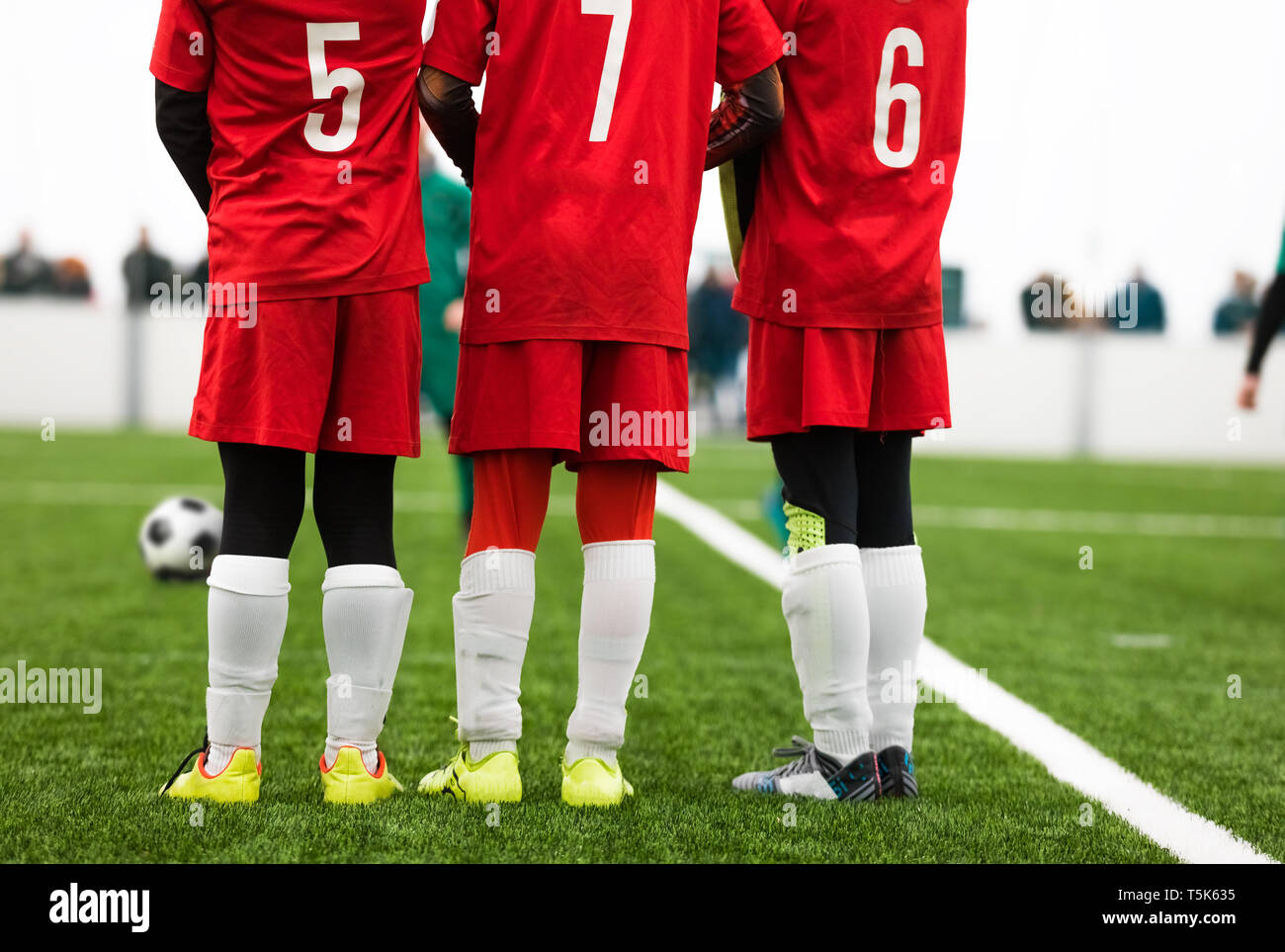 Junior Soccer Players Standing in a Wall. Free Kick Situation During Football Match. Players Wearing Red Soccer Jersey Shirts with Numbers on Back. So - Stock Image