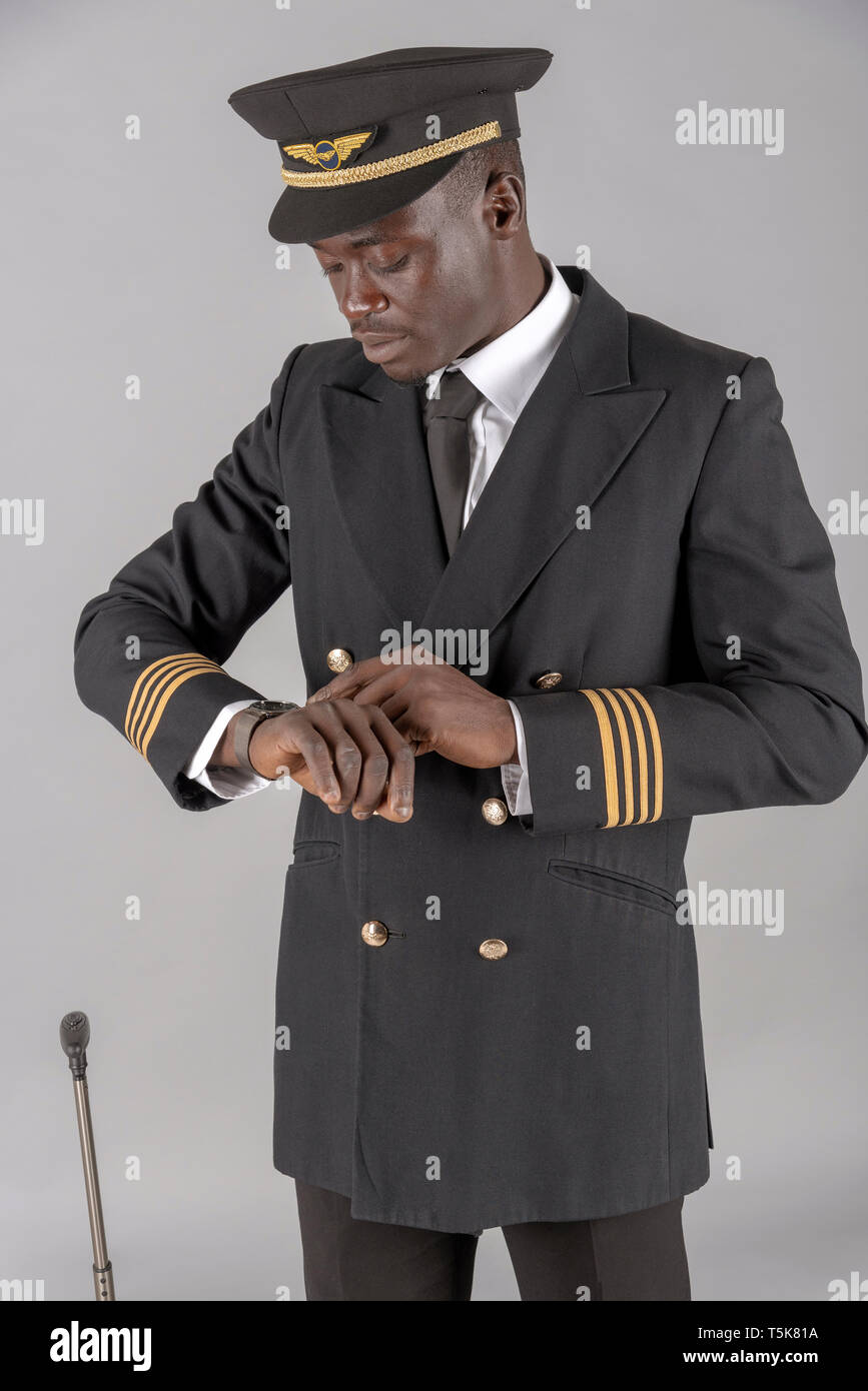 London, UK. April 2019. An airline pilot wearing his captain's uniform and checking his watch for the time - Stock Image