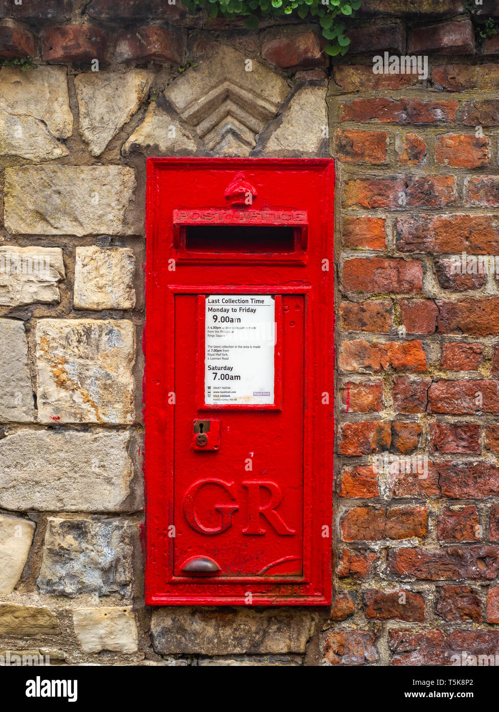 A red British post box made by A Handyside in Derby for the Royal Mail postal service in the UK - Stock Image