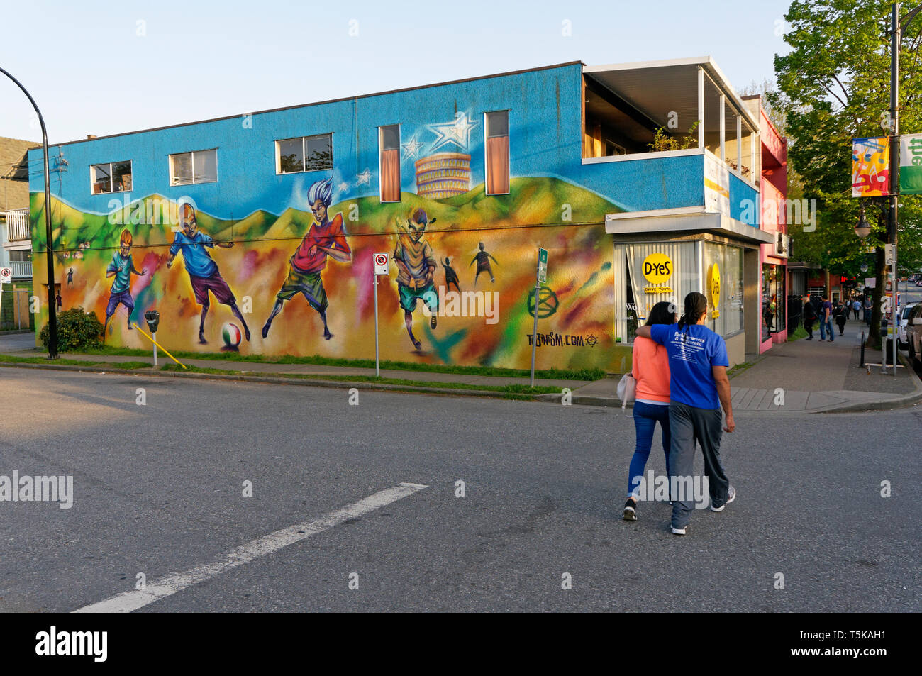 Young couple walking along Commercial Drive in Little Italy, Vancouver, BC, Canada - Stock Image