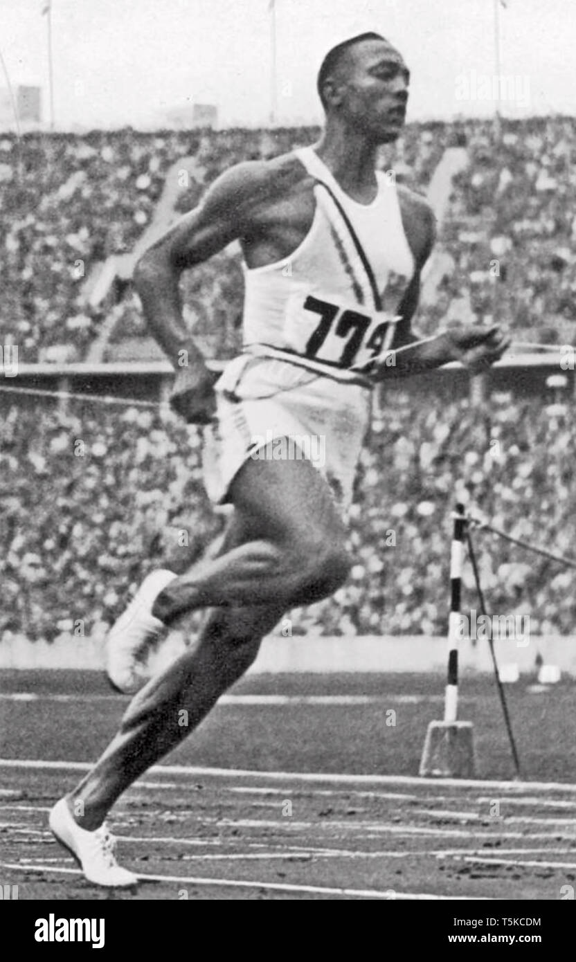 JESSE OWENS (1913-1980) American athlete winning the 100 m race at the 1936 Berlin Summer Olympics on 3 August. - Stock Image