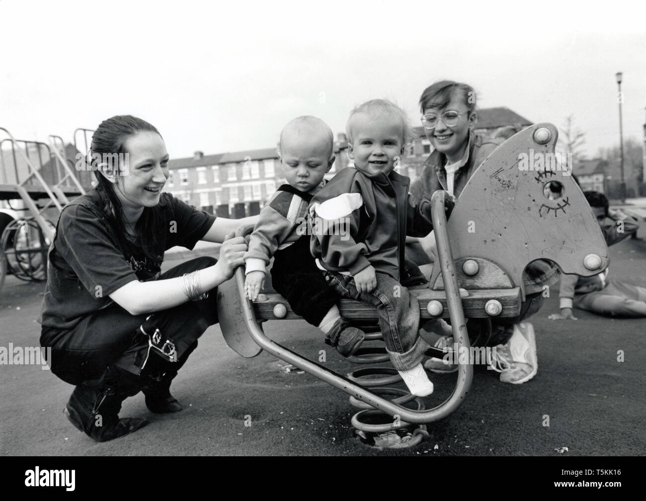 Young mothers with toddlers in playground, UK 1989 - Stock Image