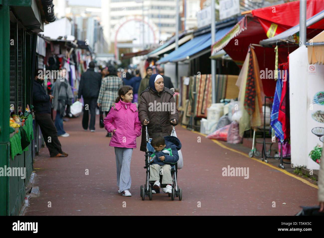 Family walking through Shepherd's Bush Market. Hammersmith, London. 28.10.2010 - Stock Image