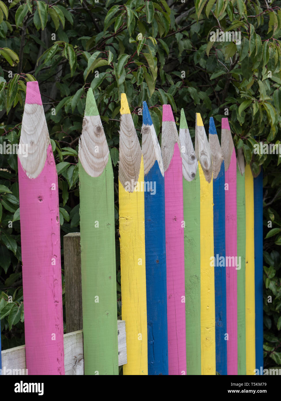 A colourful fence with posts shaped and stylised as pencils - Stock Image