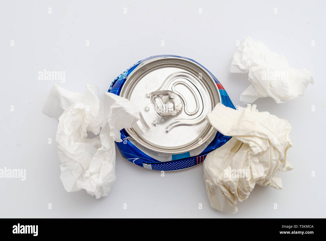 Crushed compressed aluminum can of a carbonated drink with crumpled sheets of paper. Pollution, waste, ecology. - Stock Image