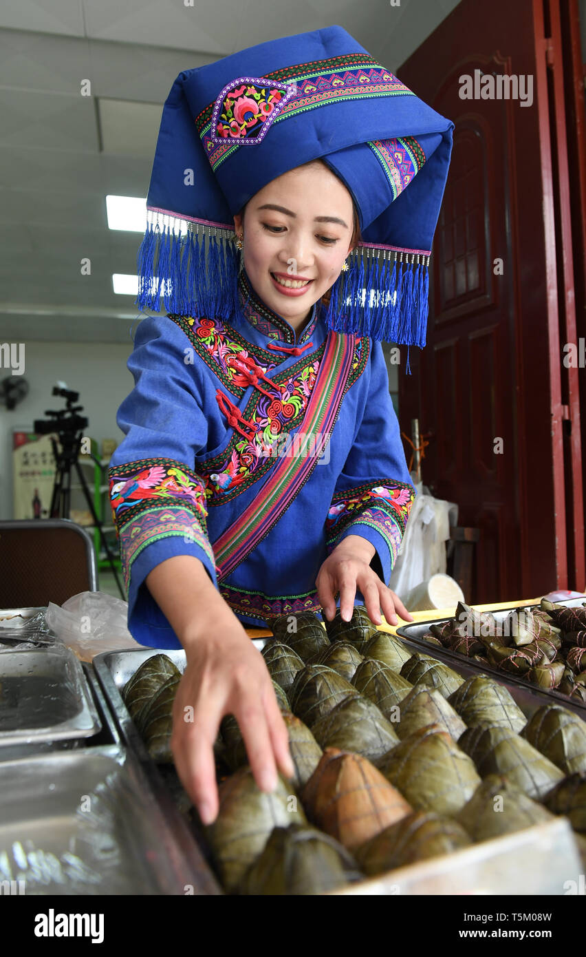 (190425) -- NANNING, April 25, 2019 (Xinhua) -- A staff member arranges glutinous rice dumplings at Equan scenic spot in Jingxi City, south China's Guangxi Zhuang Autonomous Region, April 16, 2019. Guangxi has promoted major tourism projects and brands in recent years, and the customs of border area have attracted a lot of tourists. (Xinhua/Lu Boan) Stock Photo
