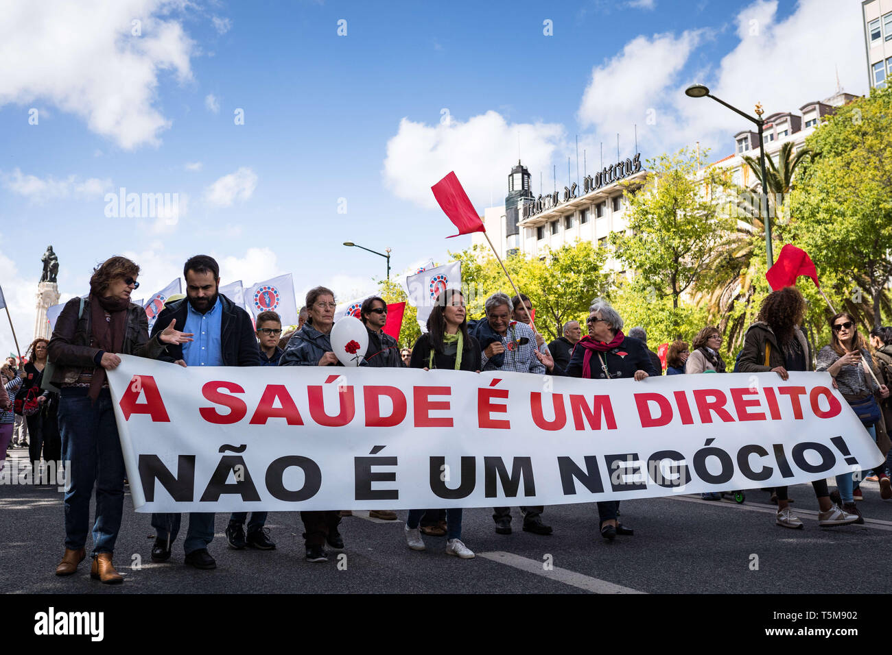 Lisbon, PORTUGAL, Portugal. 25th Apr, 2019. A poster says ''A saude e um direito, nao e um negocio'' - ''Health is a right, not a business.''.Thousands of people march in a parade to celebrate the 45th anniversary of the April 25 Revolution, also known as the Carnation Revolution, the Avenida da Liberdade in Lisbon. Credit: Henrique Casinhas/SOPA Images/ZUMA Wire/Alamy Live News - Stock Image