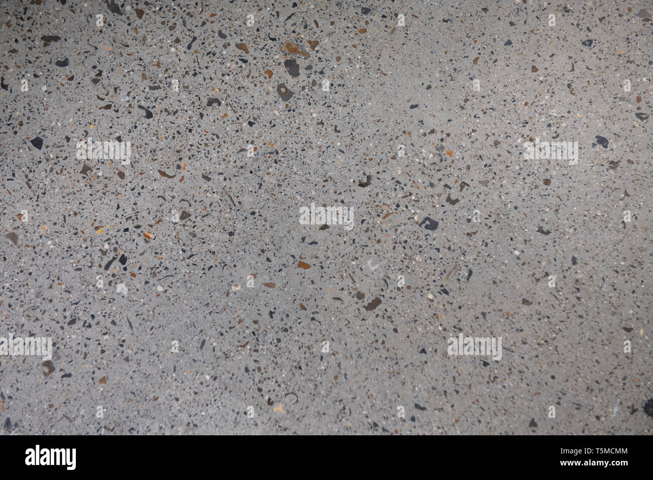 Ground Concrete floor inside building with polished gravels. - Stock Image