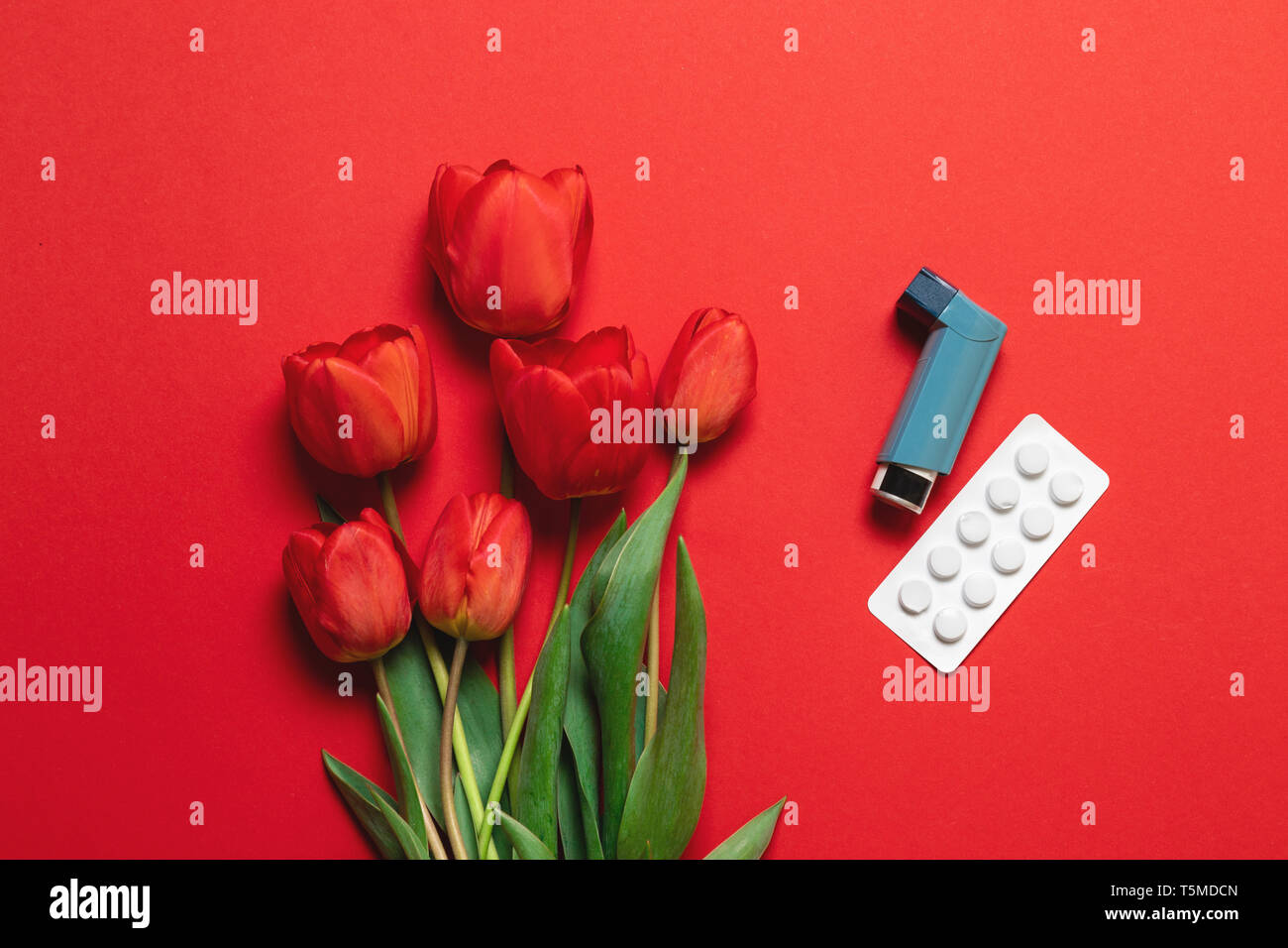 Asthma inhaler and bouquet of flowers with copy space - Stock Image