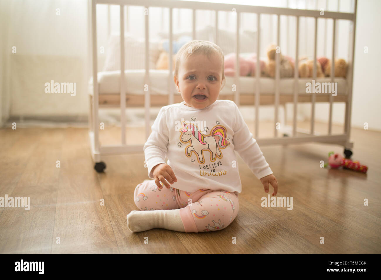 A sad toddler sits on the floor and cries against background of the crib. - Stock Image