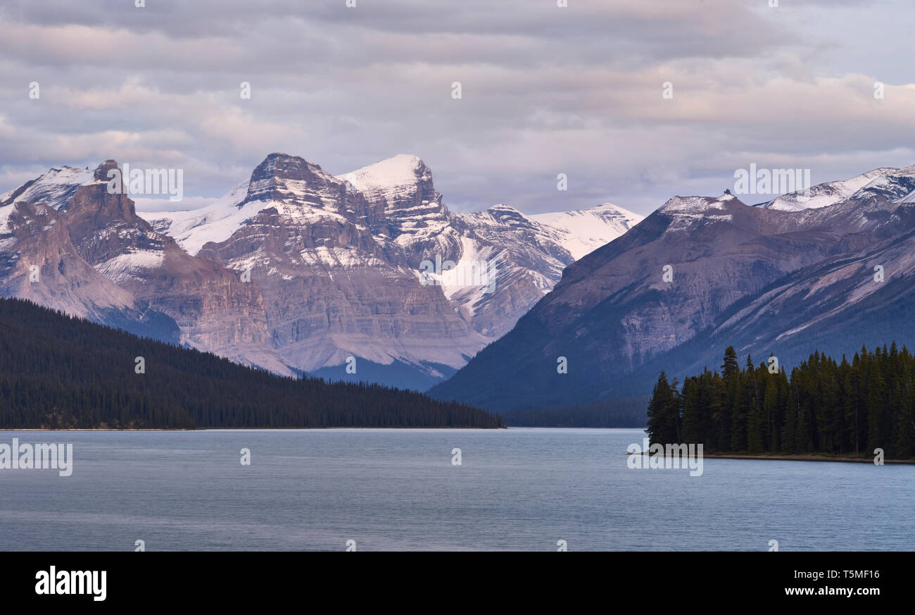 Scenic view of Maligne lake by snowcapped mountain against cloudy sky - Stock Image