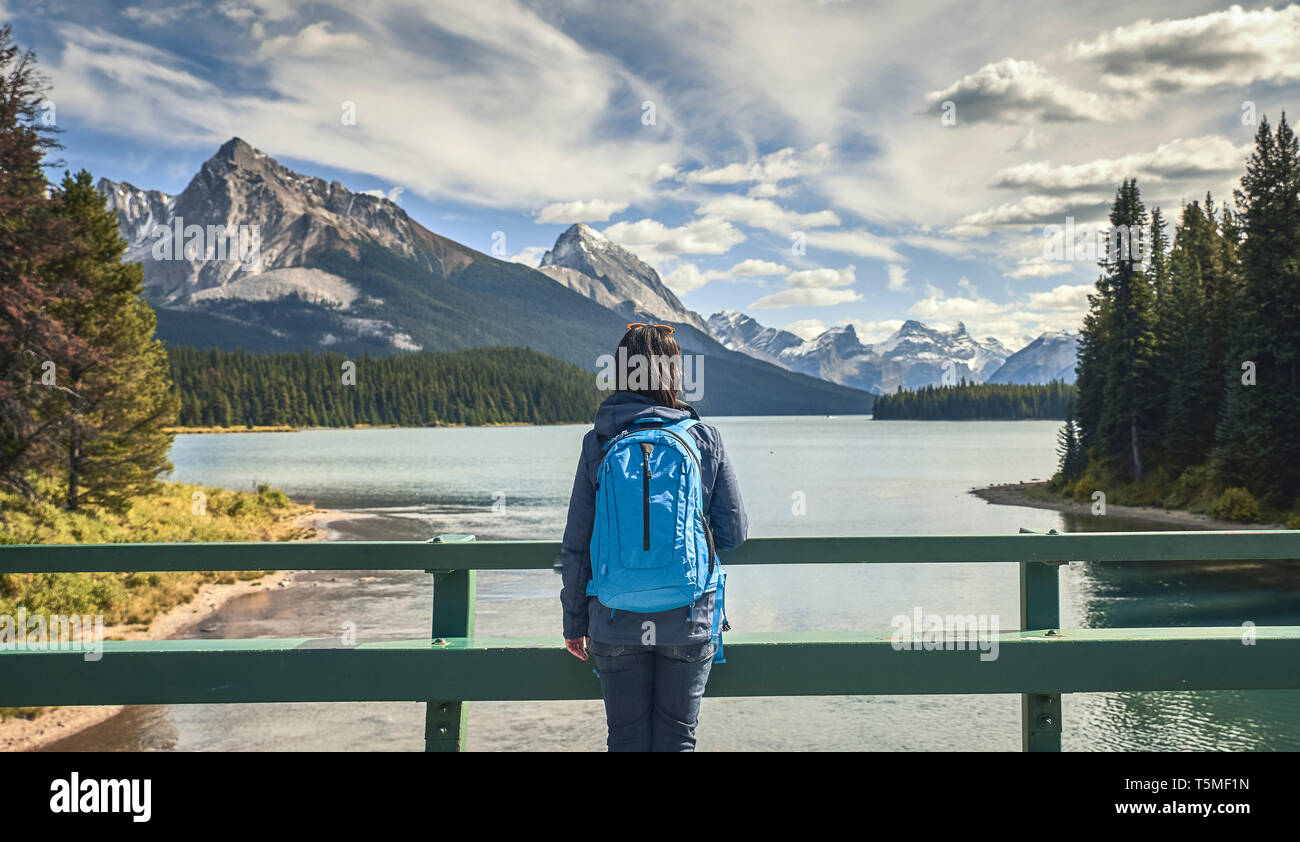 woman looking  by lake at Maligne Lake in Jasper National Park Stock Photo