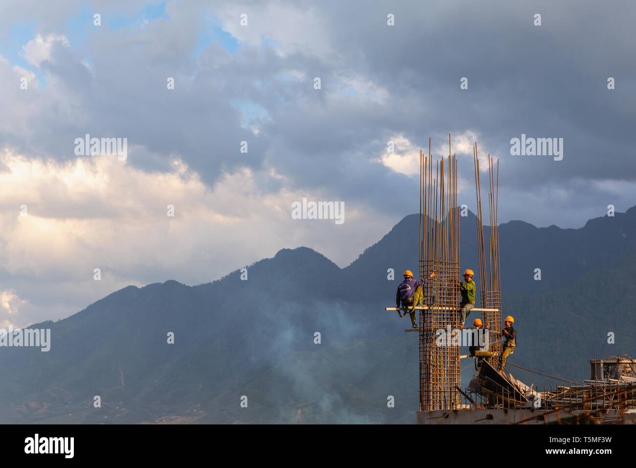 Construction workers climbing and building a high-rise development in SaPa Vietnam, Asia - Stock Image