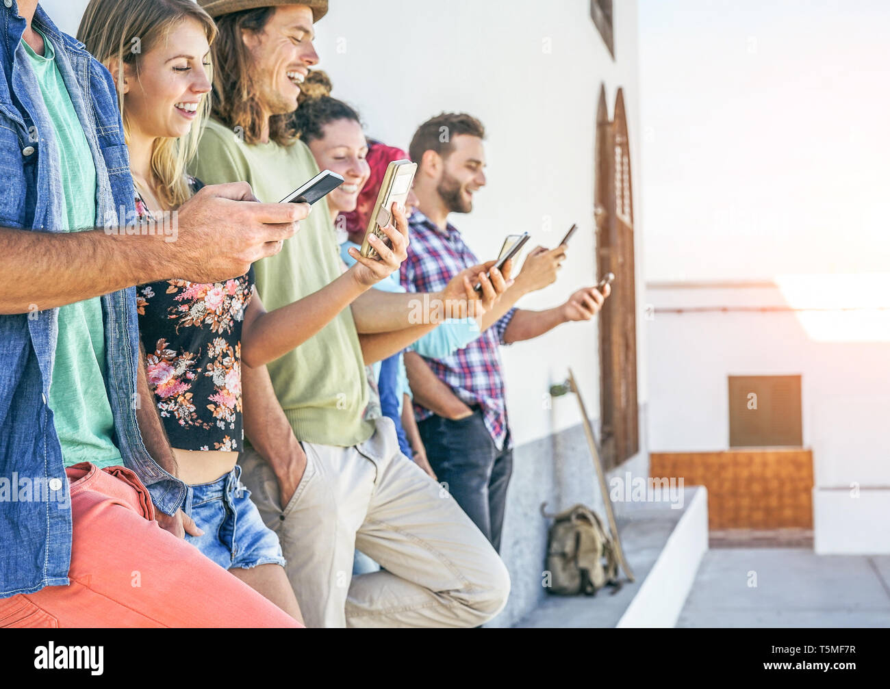Young people watching on their smart mobile phones outdoor - Generation addicted to new smartphone technology - Stock Image