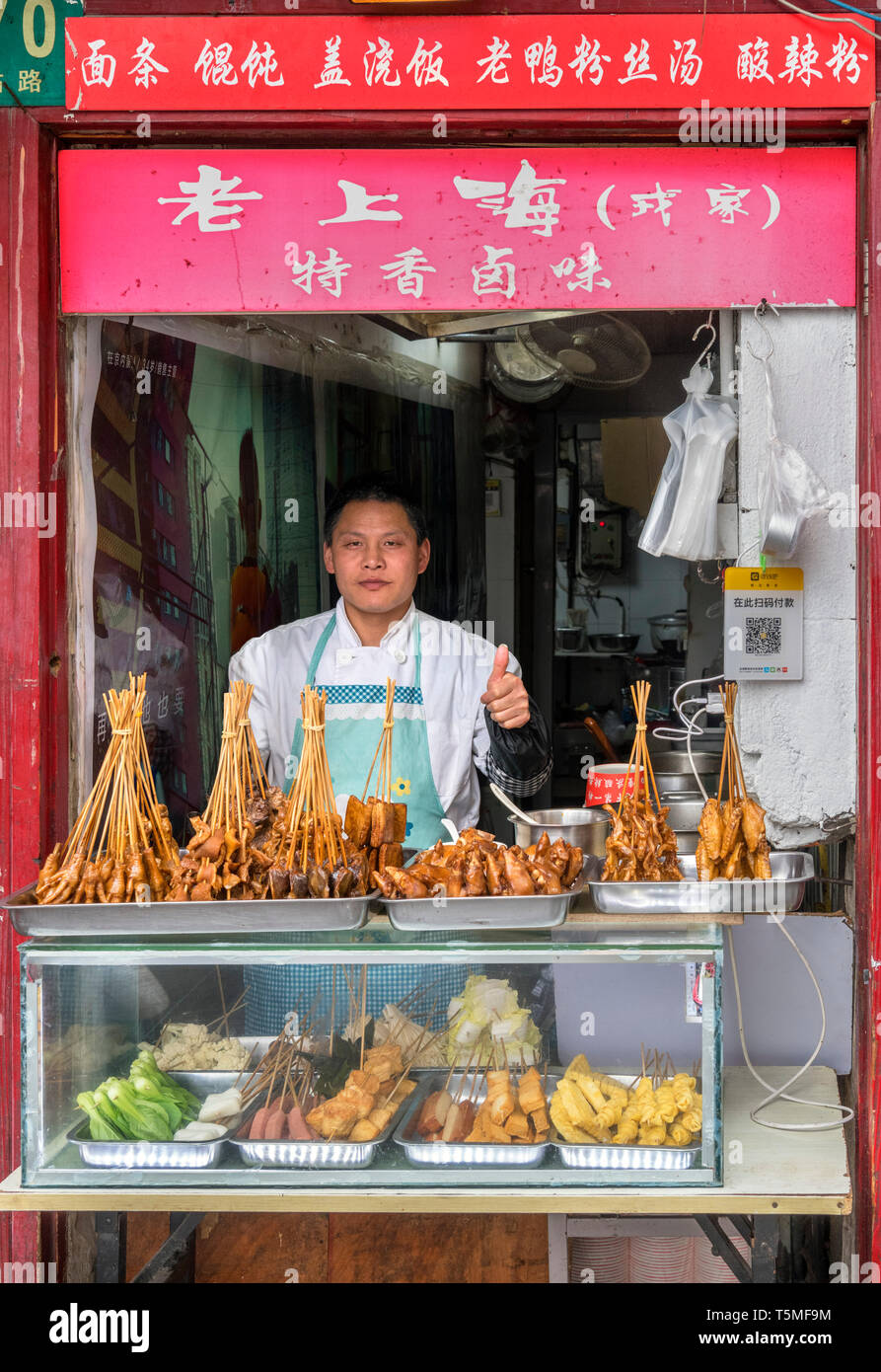 Vendor giving a thumbs up at a traditional food stall in the Old Town (Nanshi district), Shanghai, China - Stock Image