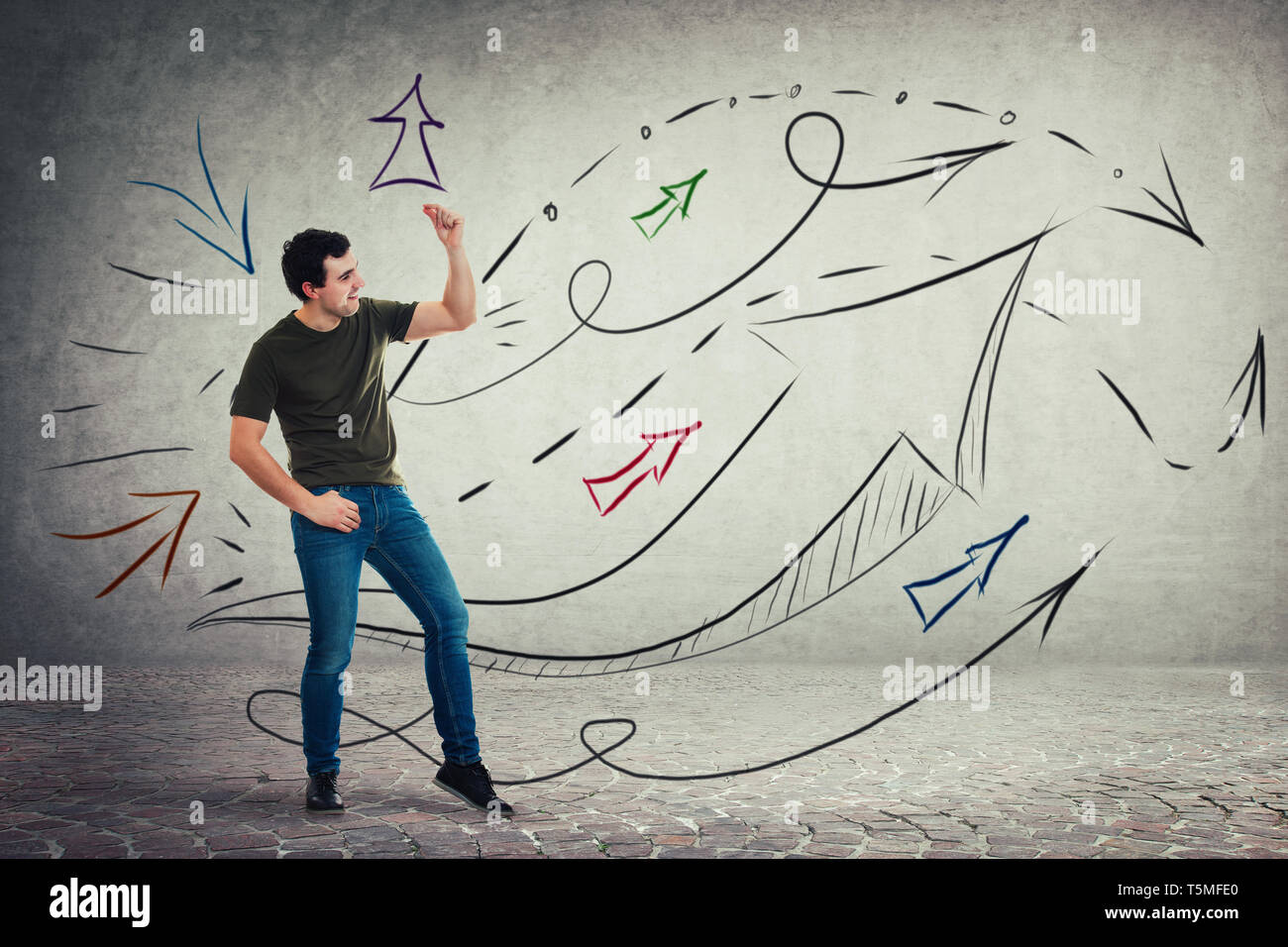 Contented casual young man dancing by the music, moves feeling the rhythm, funny entertainer. Arrows and lines going up as body language expression. - Stock Image