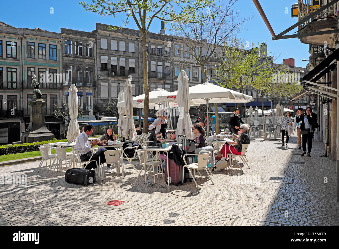 People sitting eating and drinking at outside tables on a patio pavement restaurant with umbrellas in spring sunshine Porto Portugal  KATHY DEWITT - Stock Image