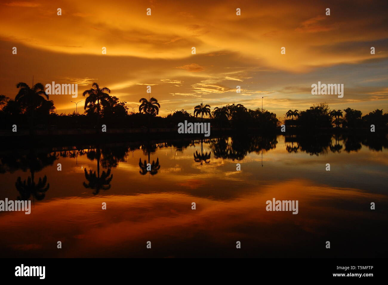 Sunset of fire over the lake and palm trees in the tropical island of Borneo in Kota Kinabalu, Malaysia. Clouds and spectacular colours fill the sky. - Stock Image