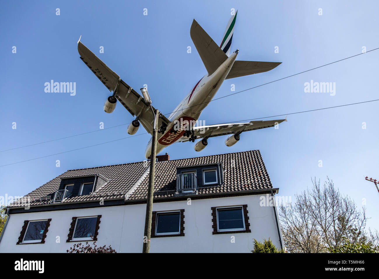 Aircraft landing on DŸsseldorf International Airport, DUS, Germany, houses in Lohausen district, directly at the runway, - Stock Image