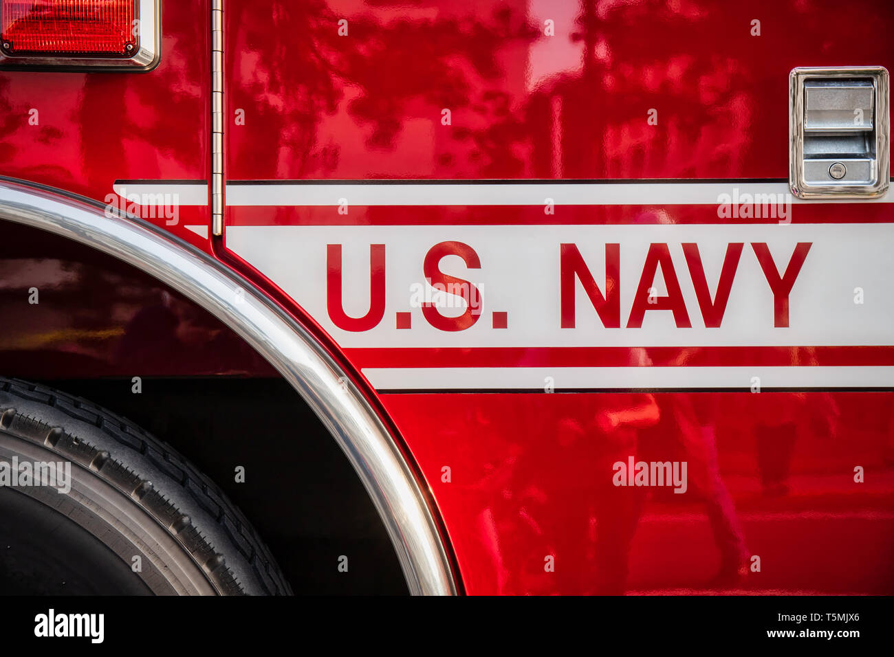 A crowd reflects on the door of a US Navy fire truck on display at Naval Base Yokosuka. Stock Photo