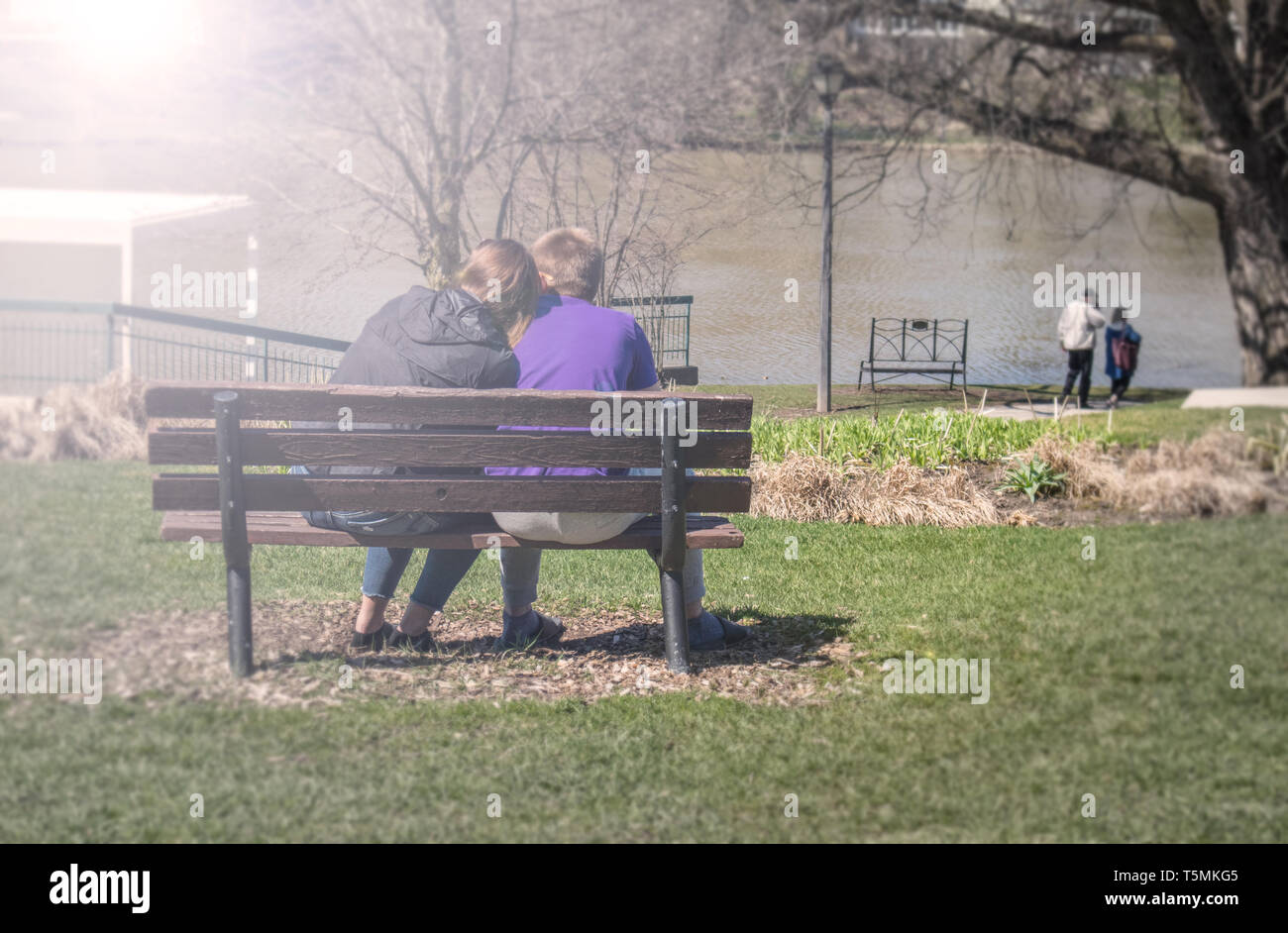 A couple sitting on a park bench. She tenderly lays her head on his shoulder, during a sunny day of spring. View from behind. - Stock Image