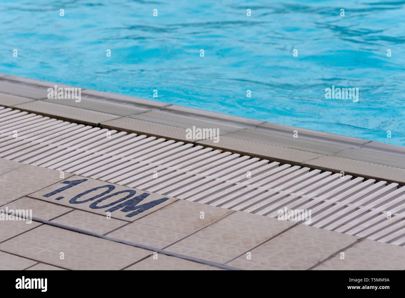 Pool side depth indicator of 1.00 meters or one meter deep. Beware. Stock Photo