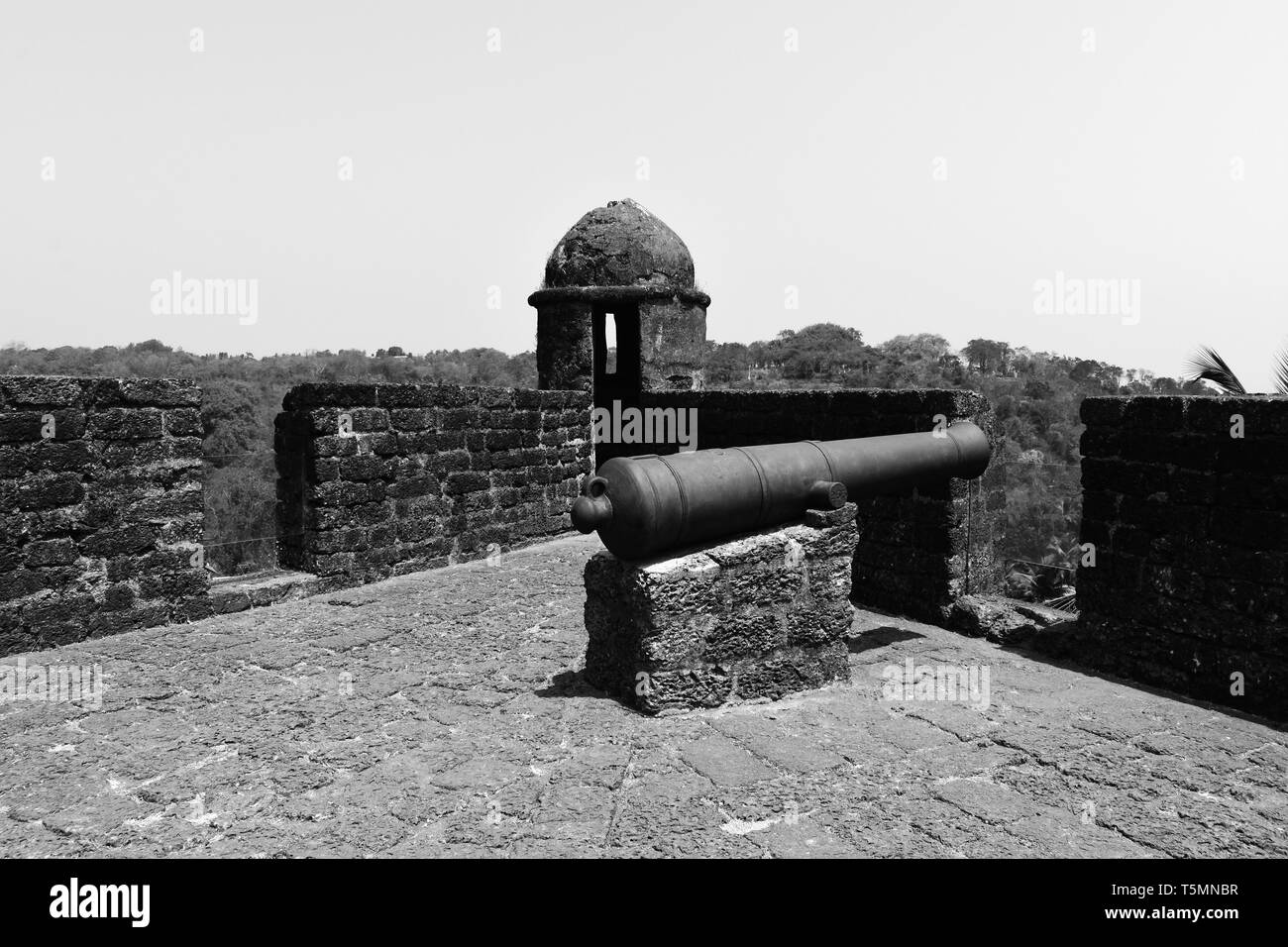 A Gun and watchtower at Reis Magos Fort in black and white. - Stock Image