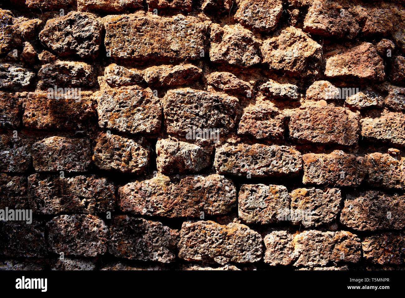 Closeup of a portion of a wall made of laterite rocks. - Stock Image