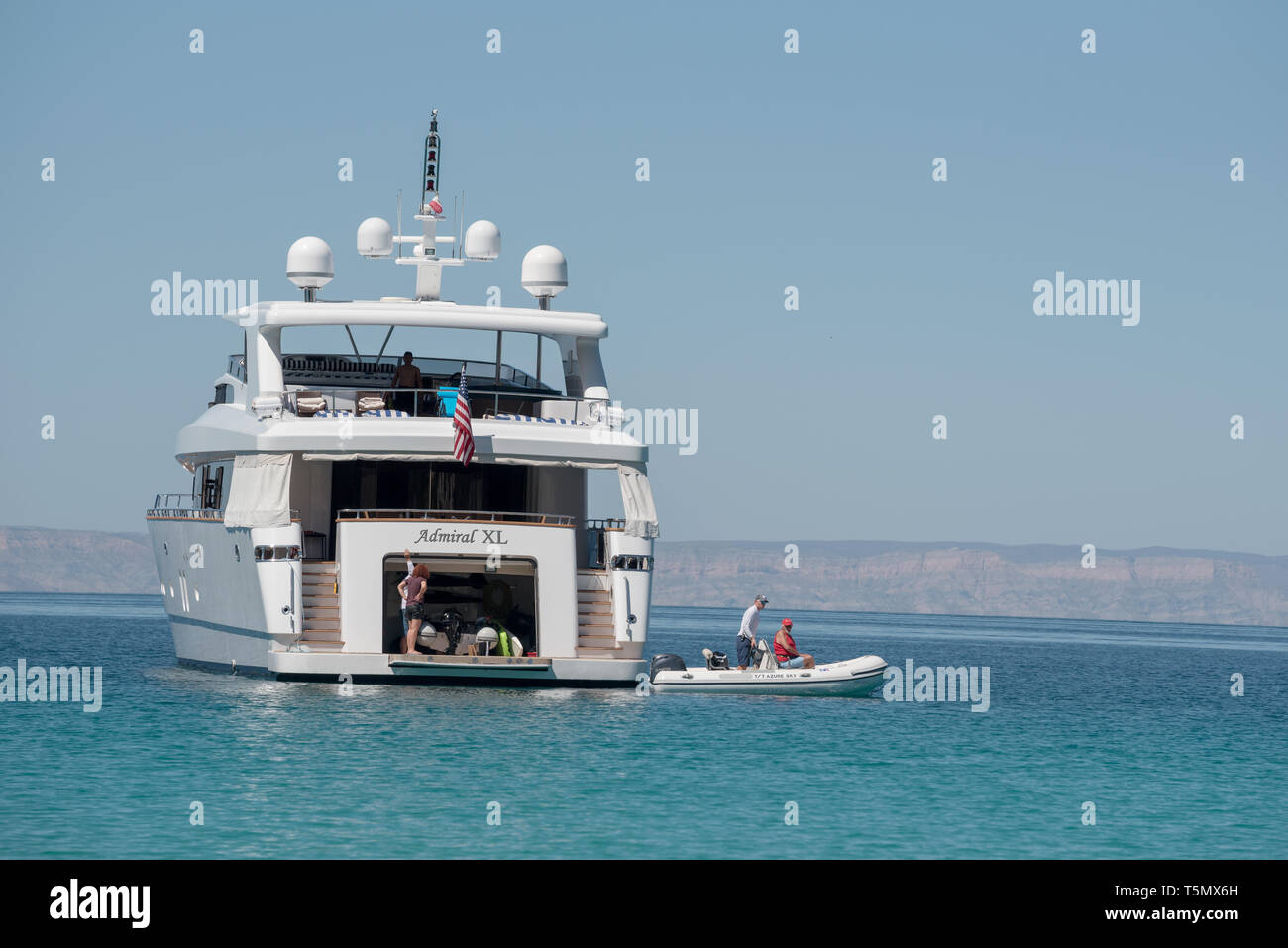 Dinghy leaving large private yacht in the Gulf of California, Baja California Sur, Mexico. - Stock Image