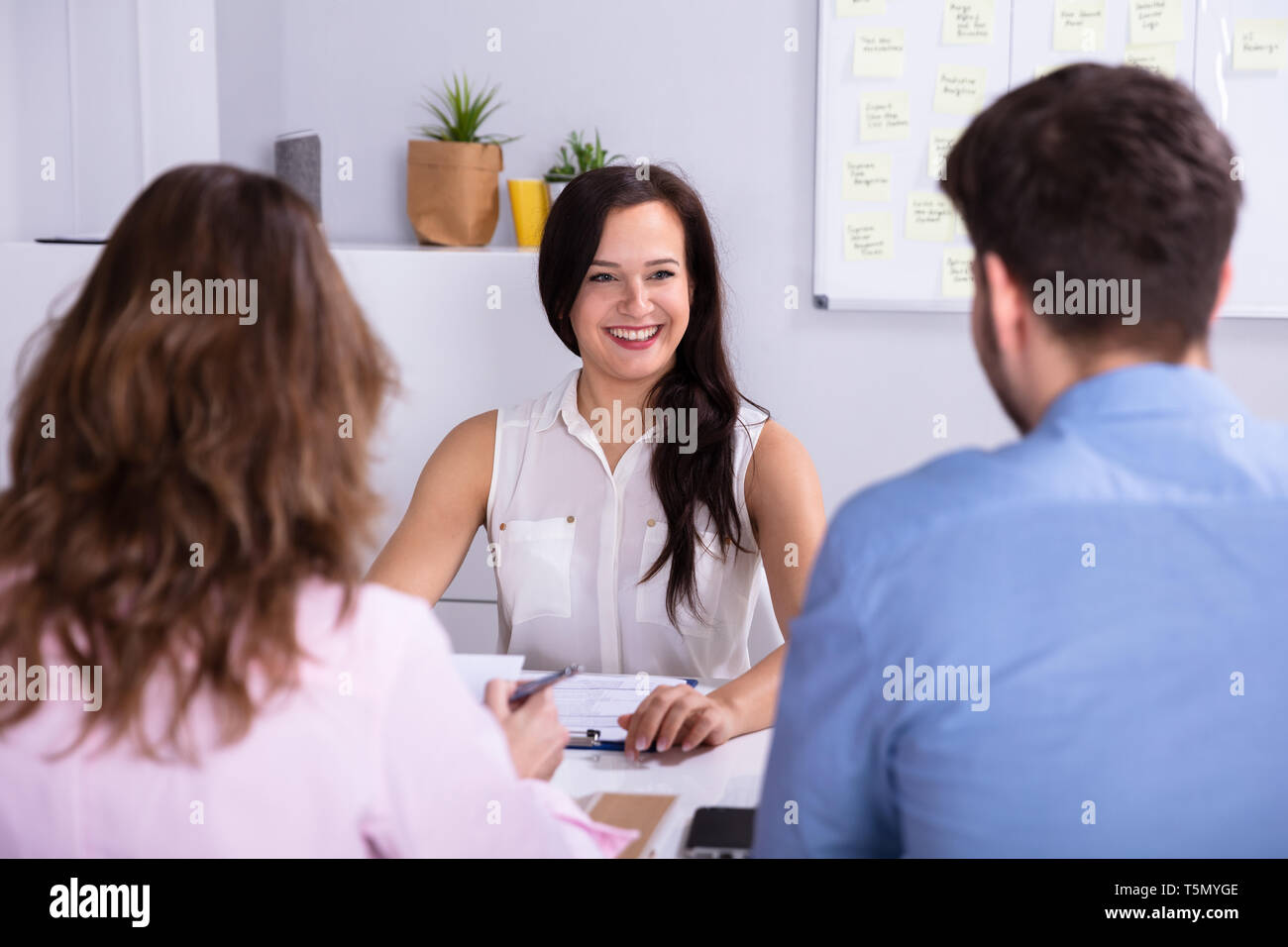 Businessman And Businesswoman Taking Interview Of Young Smiling Woman - Stock Image