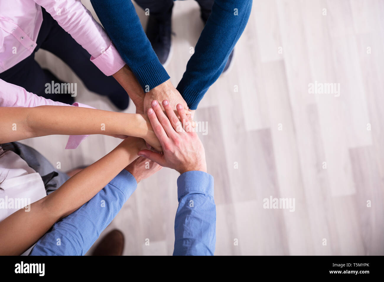 An Elevated View Of Businesspeople Stacking Hands Over Each Other - Stock Image