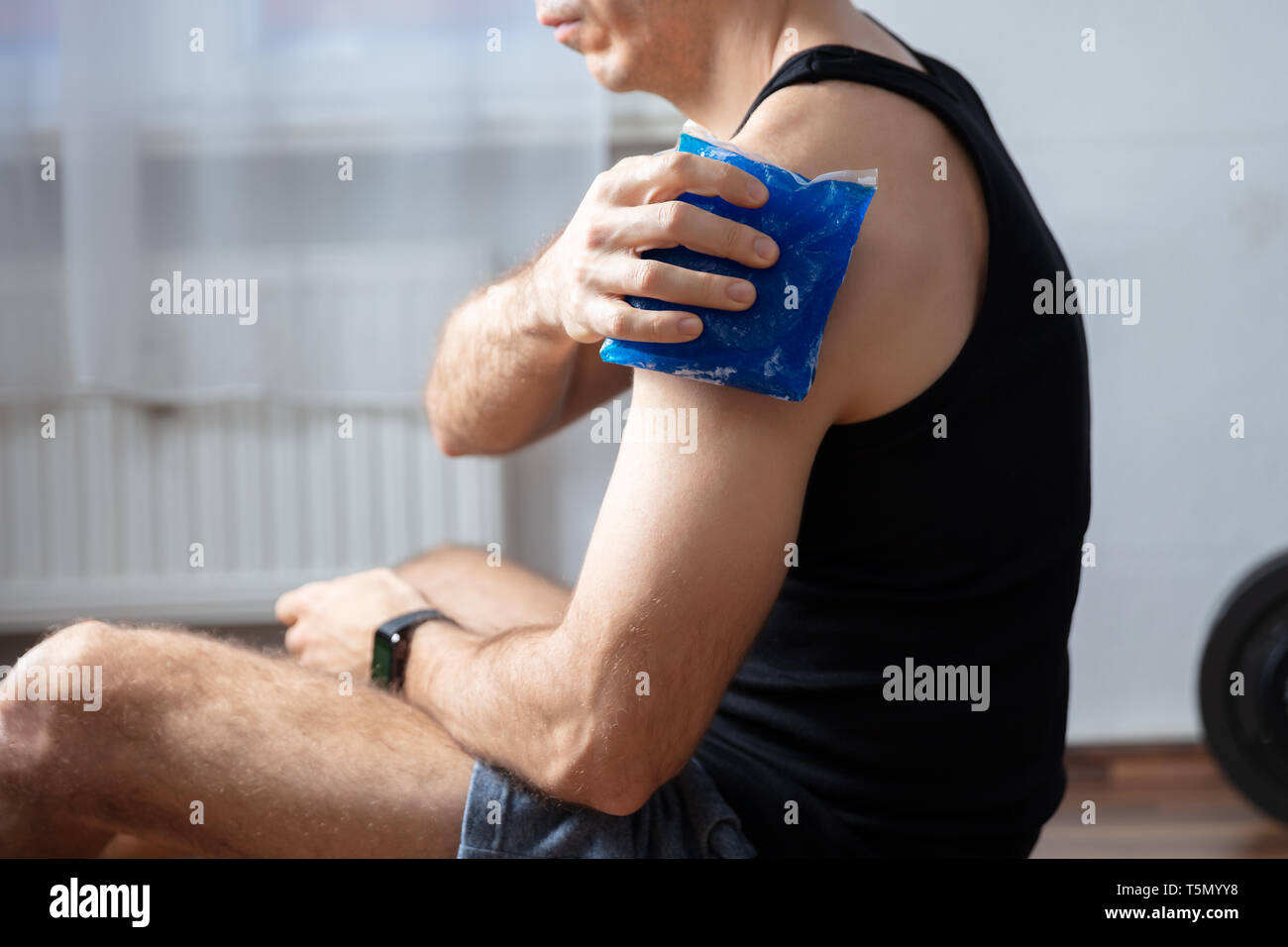Close-up Of Male Trainer Applying Cool Gel Pack On His Injured Shoulder At Gym - Stock Image