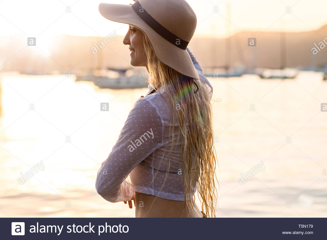 woman wearing sun hat looking at ocean in the afternoon - Stock Image