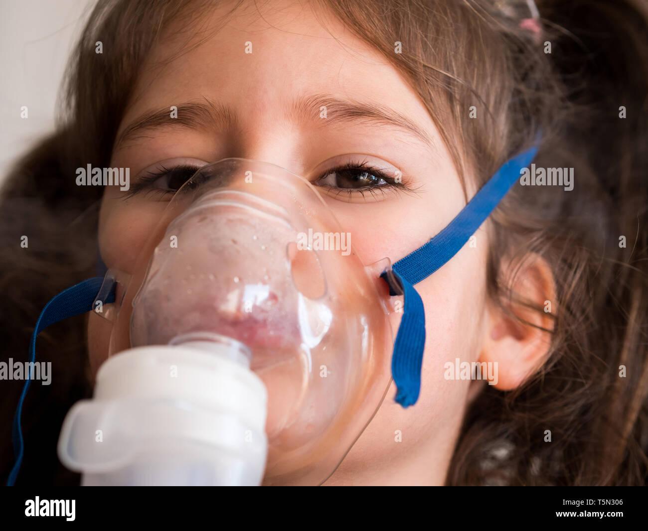Cute small girl inhaling with inhalator close up - Stock Image