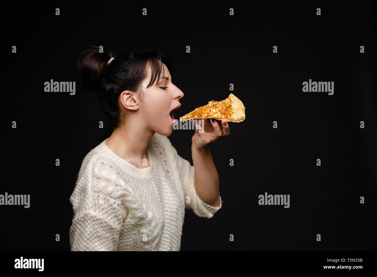 Young caucasian woman with tail eating piece of pizza. - Stock Image