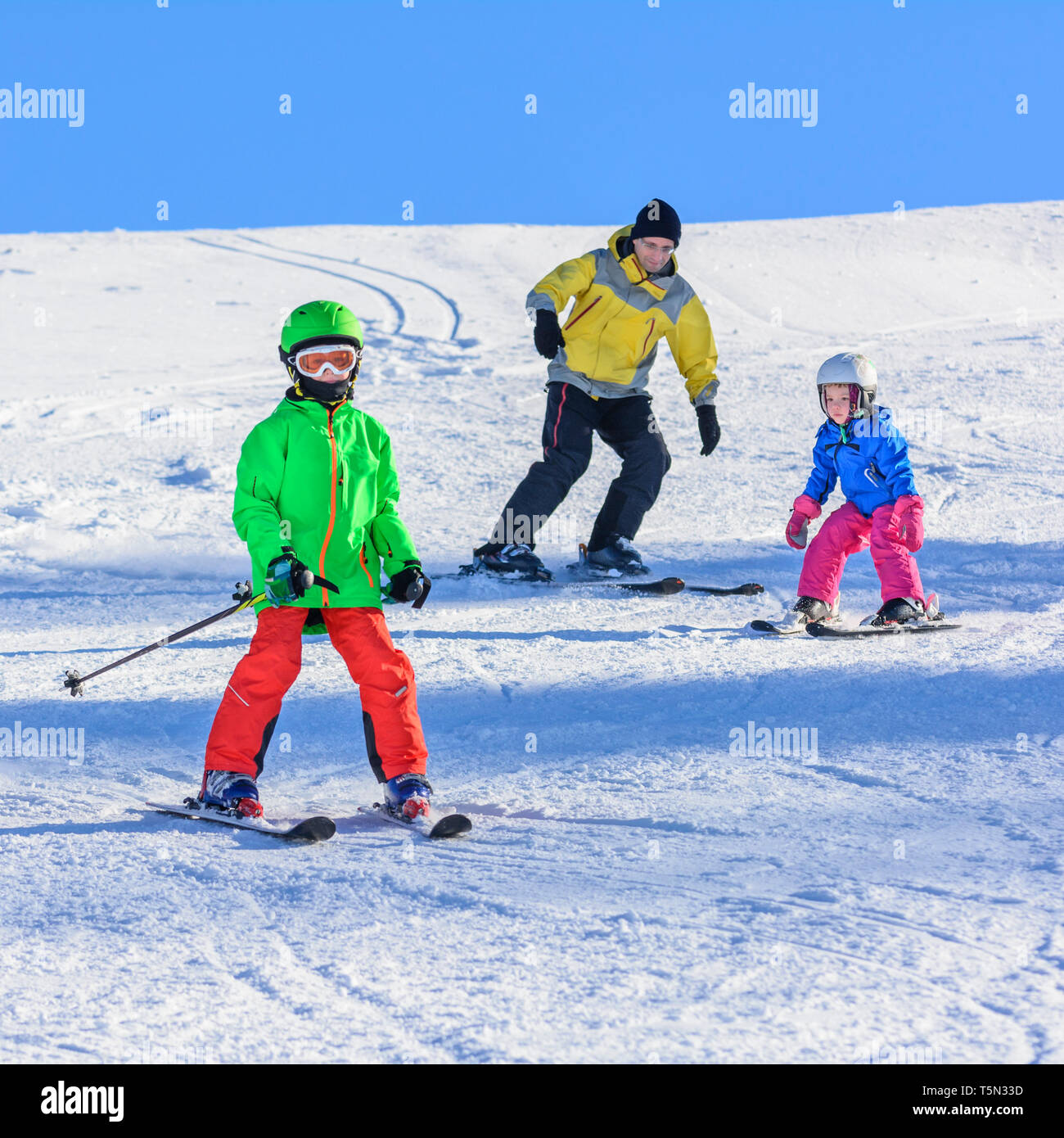 Skiing with the kids on sunny winter day - Stock Image