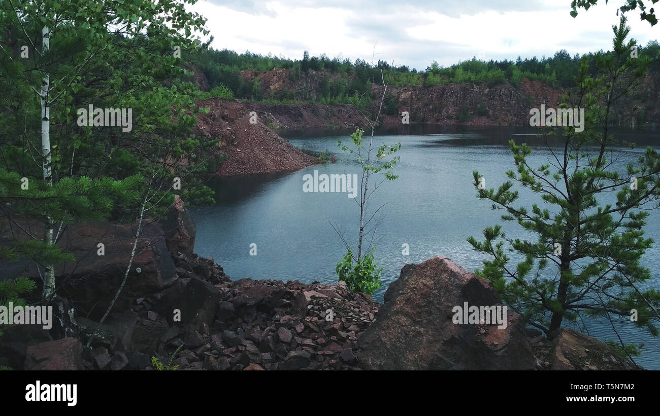 View on inactive abandoned granite quarry with beautiful blue water - Stock Image