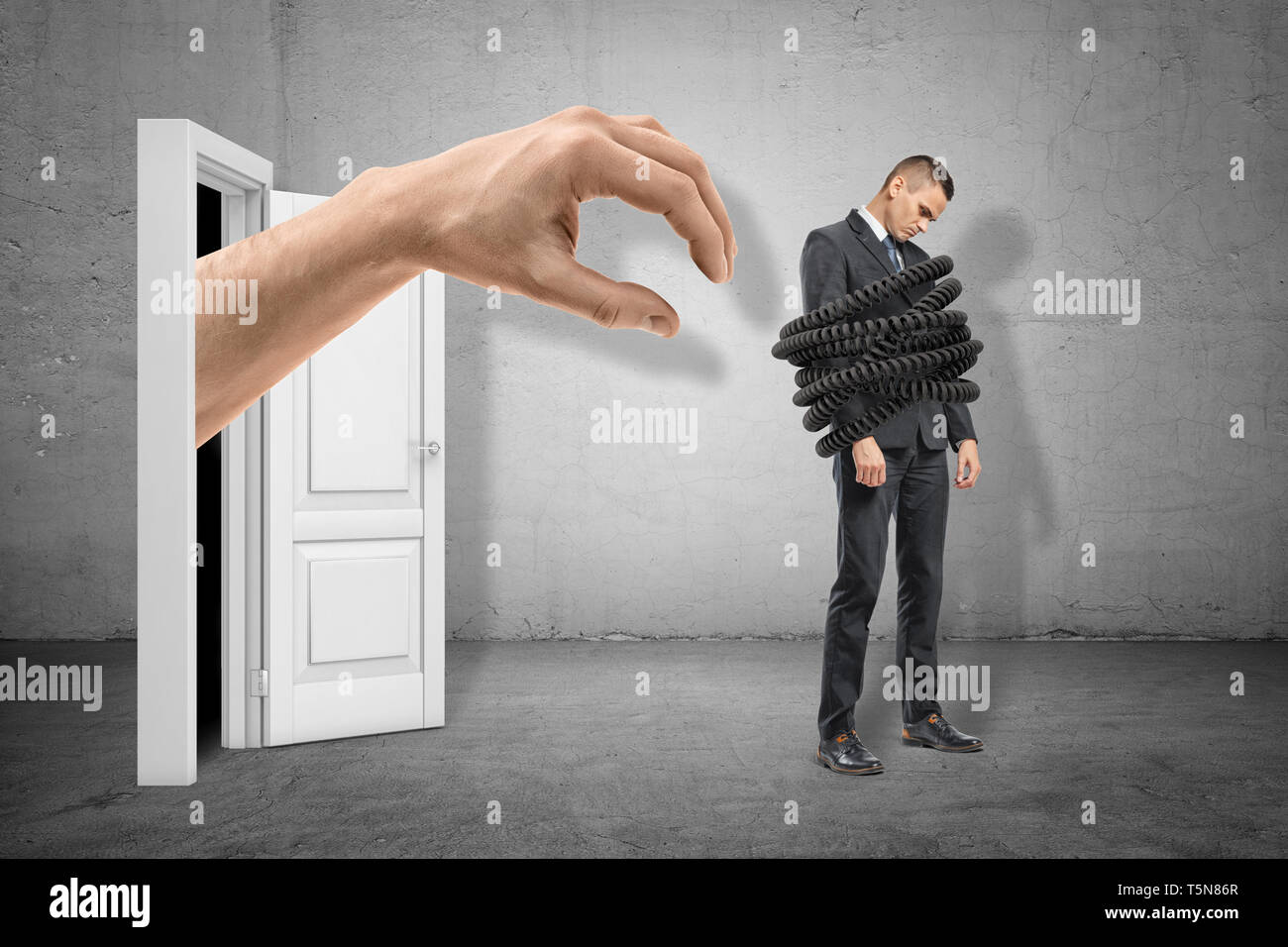 Big hand reaching to young sad businessman tied up with telephone cord on grey wall background - Stock Image